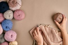 Конец-вверх женских рук вязать цвет бежа свитера или шотландки шерстей Взгляд сверху Стоковые Фото