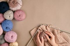 Конец-вверх женских рук вязать цвет бежа свитера или шотландки шерстей Взгляд сверху Стоковая Фотография