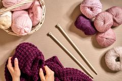 Конец-вверх женских рук вязать цвет сирени свитера или шотландки шерстей Взгляд сверху Стоковое фото RF