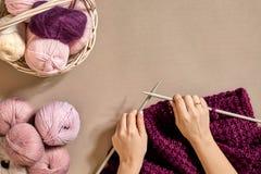 Конец-вверх женских рук вязать цвет сирени свитера или шотландки шерстей Взгляд сверху Стоковые Изображения RF