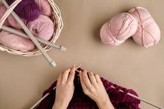 Конец-вверх женских рук вязать цвет сирени свитера или шотландки шерстей Взгляд сверху Стоковая Фотография RF