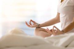 Конец вверх женских рук в жесте mudra, отменянной кровати Стоковое фото RF