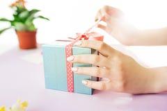 Конец-вверх женских рук держа настоящий момент Ультрамодный розовый стол Стоковые Фото