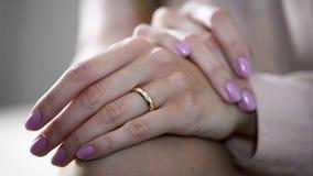 Конец-вверх женских рук лежа на коленях с обручальным кольцом золота, ювелирными изделиями Стоковые Фото
