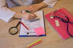 Конец вверх женского доктора медицины заполняя терпеливую ручку документа на белом столе в больнице концепция доктора в больнице Стоковые Фотографии RF