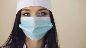 Конец вверх женской стороны ` s хирурга носит хирургическую маску в 4K акции видеоматериалы