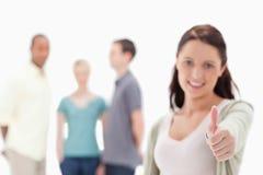 Конец-вверх женщины давая большие пальцы руки-вверх с друзьями Стоковые Фотографии RF
