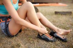 Конец-вверх женщины альпиниста утеса сильной кладя на взбираясь ботинки пока сидящ на траве Sporty здоровая тонкая девушка Стоковое Изображение