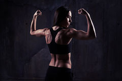 Конец-вверх женщины в хорошей форме показывая ее бицепс, tricep Стоковое Изображение