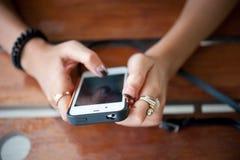 Конец-вверх женщины держа мобильный телефон, девушку используя smartphone внутри Стоковое фото RF