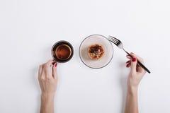 Конец-вверх женщины есть торт и выпивая чай Стоковое фото RF