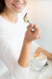 Конец вверх женщины есть торт на кафе или доме Стоковые Фото