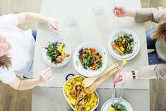 Конец-вверх женщины имея обедающий с зажаренный в духовке chiken при картошка, который служат с зеленым салатом Стоковая Фотография
