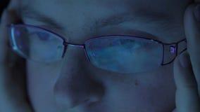 Конец-вверх женщины наблюдает смотрящ монитор, работая с компьютером, компьтер-книжка Свет монитора отражен в глазах акции видеоматериалы