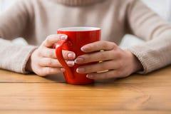 Конец-вверх женщины с чашкой горячего питья Стоковое Изображение