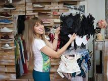 Конец-вверх жизнерадостной женщины стоя в магазине одежды и выбирая сексуальное нижнее белье Shopaholic на a Стоковая Фотография