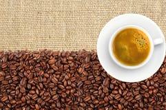 Конец-вверх зажаренных в духовке кофейных зерен и кофейной чашки над бельем Стоковое Изображение RF