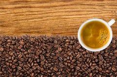 Конец-вверх зажаренных в духовке кофейных зерен и кофе чашки над деревянным Стоковая Фотография RF