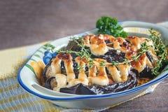 Конец-вверх заполненных томатов, мяса и луков, баклажана с соусом на блюде Стоковые Изображения