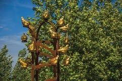 Конец-вверх золотого памятника птиц металла с густолиственным деревом в солнечном дне на Weesp стоковое фото