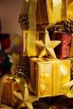 Конец-вверх золотых подарков сложенных вверх в стоге запачканном в предпосылке bokeh золота - селективном фокусе Стоковые Фотографии RF