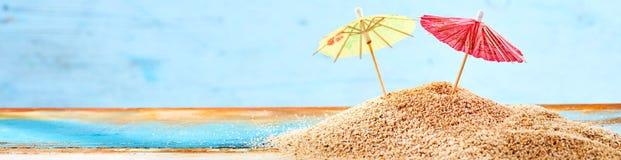 Конец-вверх 2 зонтиков коктеиля на песке Стоковое фото RF