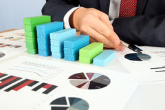 Конец-вверх диаграммы в виде вертикальных полос диаграммы здания бизнесмена на столе Стоковая Фотография