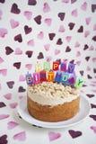 Конец-вверх именниного пирога с свечами над сердцем сформировал предпосылку Стоковые Изображения