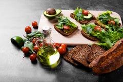 Конец-вверх ингридиентов здравицы авокадоа Отрезанный хлеб, прованский соус и здоровые свежие овощи на предпосылке таблицы Стоковые Фото