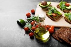 Конец-вверх ингридиентов здравицы авокадоа Отрезанный хлеб, прованский соус и здоровые свежие овощи на предпосылке таблицы Стоковое Фото