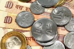Конец вверх индейца бумажные деньги 10 рупий с индийскими монетками Стоковая Фотография RF