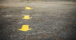 Конец-вверх дирекционных желтых стрелок покрашенных на вымощенной дороге с космосом экземпляра для текста Стоковая Фотография