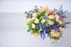 Конец-вверх искусственных цветков роз от пены цветов сини, белых в белом баке и деревянном ларце сделанных с стоковые изображения
