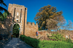 Конец-вверх каменных стены и ворот, зеленых холмов, деревьев и голубого солнечного неба в Orvieto Стоковая Фотография