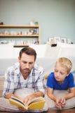 Конец-вверх книги чтения отца и сына пока лежащ на поле Стоковое Изображение RF