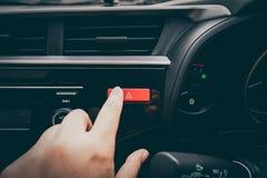 Конец-вверх кнопки отжимать руки ` s человека непредвиденной в автомобиле Стоковое фото RF
