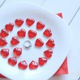 конец вверх кольцо и красные сердца на белой плите Стоковое Изображение