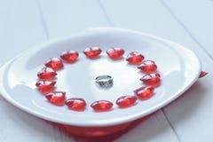 конец вверх кольцо и красные сердца на белой плите Стоковое Фото