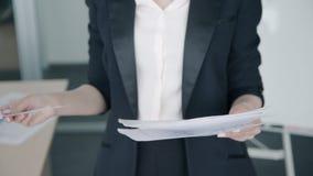 Конец вверх коммерсантки проверяя бумажный отчет стоя в офисе видеоматериал
