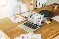 Конец-вверх компьтер-книжки с диаграммами, диаграммами, диаграммами на экране на деревянном столе Рядом бумажные графики, цифрова стоковое фото rf