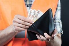 Конец-вверх конструктора держа бумажник с деньгами Стоковая Фотография