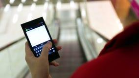 Конец-вверх короткий женщины печатая на приборе smartphone пока двигающ дальше эскалатор видеоматериал