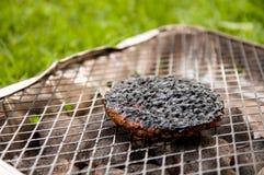 Конец-вверх, который сгорели бургера на гриле в парке Селективный фокус Стоковое Изображение RF