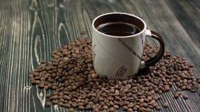 Конец-вверх кофейной чашки с зажаренными в духовке кофейными зернами на деревянной предпосылке акции видеоматериалы