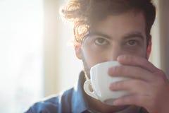 Конец-вверх кофе молодого клиента выпивая на кафе Стоковая Фотография