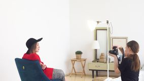 Конец-вверх красивого молодого фотографа в профессиональной студии фотографируя модель в черной шляпе и красном платье акции видеоматериалы