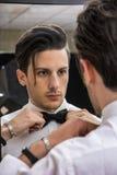 Конец-вверх красивого человека в бабочке смотря зеркало Стоковые Фото