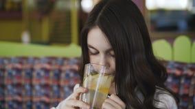 Конец вверх красивой девушки выпивает лимонад и усмехаться на камере 4K акции видеоматериалы