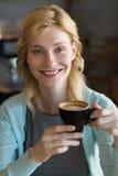 Конец-вверх красивой женщины имея кофе Стоковые Фотографии RF