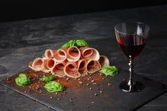 Конец-вверх красного бокала и отрезанной ветчины с шпинатом и перцем на черной предпосылке Здоровый, очень вкусный и сладостный Стоковые Фото